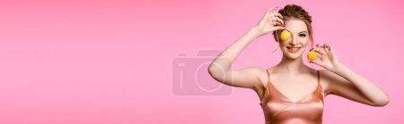 Photo pour Souriant élégante belle femme blonde en robe de soie tenant abricots isolés sur rose, plan panoramique - image libre de droit