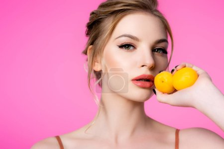 Photo pour Élégante belle femme blonde tenant des abricots isolés sur rose - image libre de droit