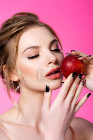 elegant beautiful blonde woman with closed eyes holding peach isolated on pink
