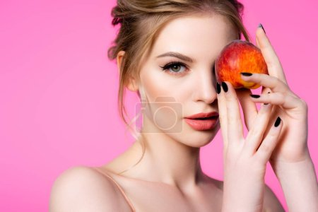 Photo for Elegant beautiful blonde woman holding peach isolated on pink - Royalty Free Image