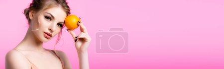 Photo pour Élégante belle femme blonde tenant orange mûr isolé sur rose, plan panoramique - image libre de droit