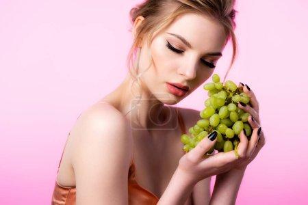 Photo pour Élégante belle femme blonde tenant des raisins verts isolés sur rose - image libre de droit