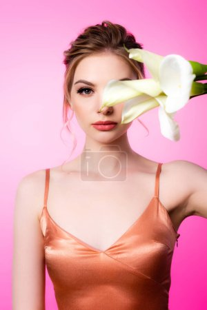 Photo for Elegant beautiful blonde woman holding calla flowers in front of face isolated on pink - Royalty Free Image