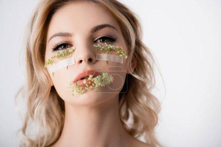 Photo pour Belle femme blonde aux fleurs sauvages sous les yeux et dans la bouche isolée sur blanc - image libre de droit