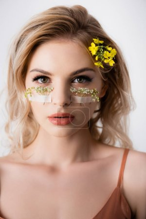 Photo for Beautiful blonde woman with wildflowers under eyes isolated on white - Royalty Free Image
