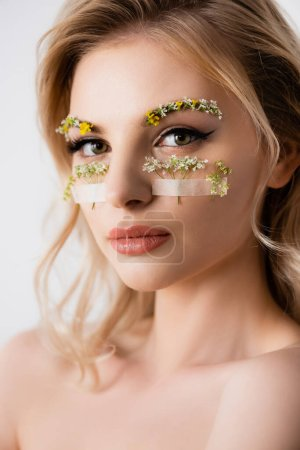 naked beautiful blonde woman with wildflowers under eyes isolated on white