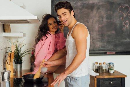 Photo pour Concentration sélective de l'homme souriant à la caméra tout en cuisinant près de petite amie avec un verre de vin dans la cuisine - image libre de droit
