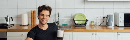 Panoramic shot of handsome man smiling at camera and holding cup of coffee in kitchen