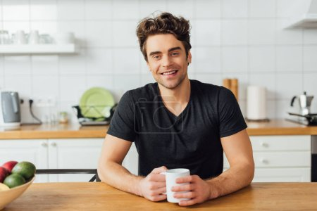 Photo for Selective focus of young man smiling at camera while holding coffee cup at table in kitchen - Royalty Free Image