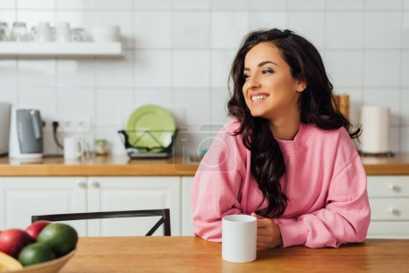 Photo for Selective focus of beautiful brunette woman smiling and holding cup of coffee at table in kitchen - Royalty Free Image