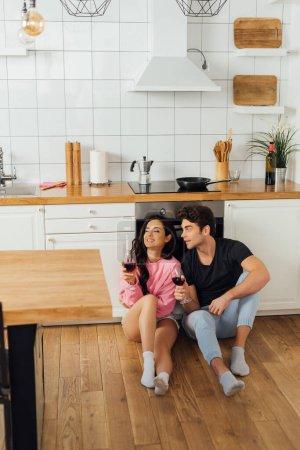 Foto de Enfoque selectivo del hombre guapo con copa de vino mirando a la novia sonriente en el suelo en la cocina - Imagen libre de derechos