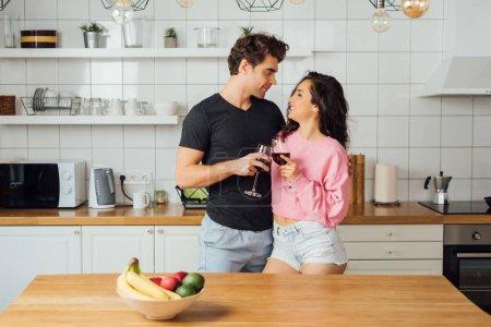 Photo pour Foyer sélectif de sourire fille clinking vin avec beau petit ami dans la cuisine - image libre de droit