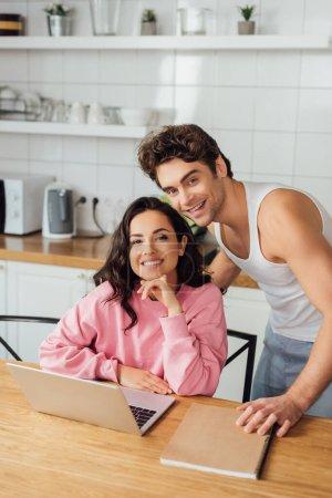 Photo pour Concentration sélective de jeunes couples positifs regardant la caméra près du portable et de l'ordinateur portable sur la table de cuisine - image libre de droit