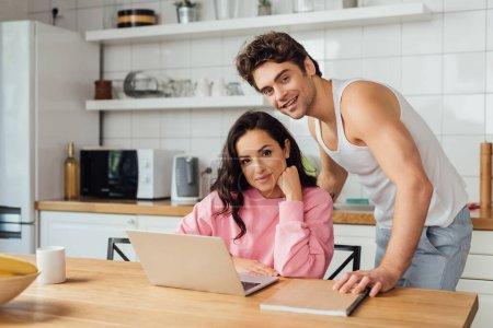 Selektiver Fokus eines lächelnden Paares, das in die Nähe von Laptop, Notizbuch und Kaffeetasse auf dem Küchentisch blickt