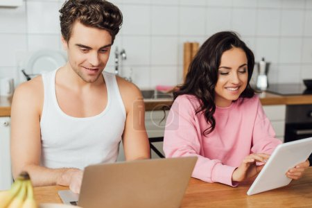 Selective focus of smiling couple using laptop and digital tablet on kitchen table