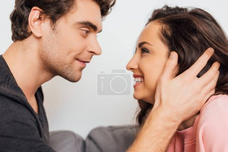 Photo for Handsome man touching hair of smiling girlfriend on couch isolated on grey - Royalty Free Image