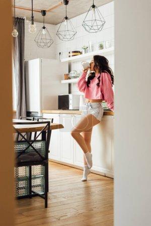 Foto de Enfoque selectivo de la hermosa morena bebiendo café en la cocina - Imagen libre de derechos