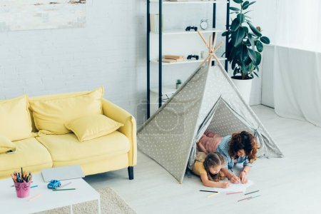 high angle view of young nanny and child drawing together while lying in kids wigwam