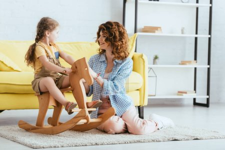 smiling nanny sitting on floor and touching adorable kid riding rocking horse