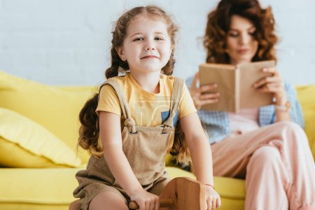 selective focus of smiling child riding rocking horse and smiling at camera while nanny reading book
