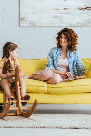 smiling nanny looking at kid riding rocking horse while sitting on sofa with book