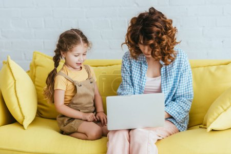 cute child sitting near young babysitter working on laptop