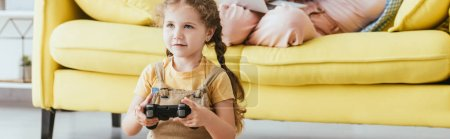 Photo for KYIV, UKRAINE - JUNE 19, 2020: cropped view of nanny on sofa and kid playing video game with joystick, horizontal image - Royalty Free Image