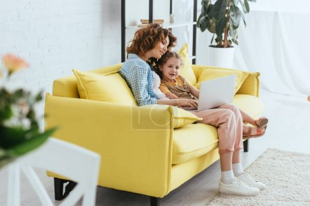 selective focus of young nanny and cute kid using laptop while sitting on sofa