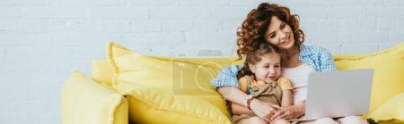 Foto de Imagen horizontal de la niñera sonriente y el niño sentado en el sofá y utilizando el ordenador portátil - Imagen libre de derechos