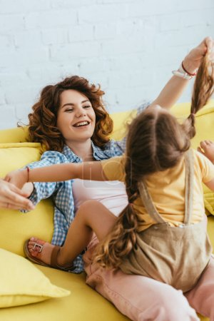 selective focus of happy babysitter having fun with child while sitting on sofa