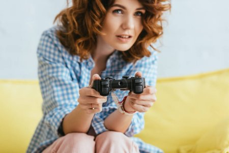 Photo for KYIV, UKRAINE - JUNE 19, 2020: selective focus of young woman playing video game with joystick - Royalty Free Image