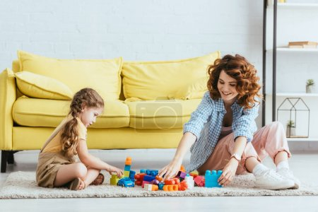 Photo for Smiling babysitter and cute kid playing with building blocks while sitting on floor near yellow sofa - Royalty Free Image