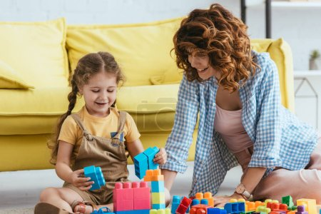 Photo for Cheerful babysitter and child playing with building blocks while sitting on floor - Royalty Free Image