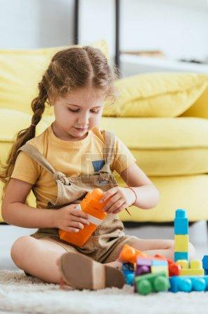 Photo pour Foyer sélectif de l'enfant adorable assis sur le sol et jouer avec des blocs de construction multicolores - image libre de droit