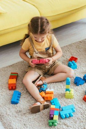 vista de ángulo alto del niño sentado en el suelo y jugando con bloques de construcción multicolores