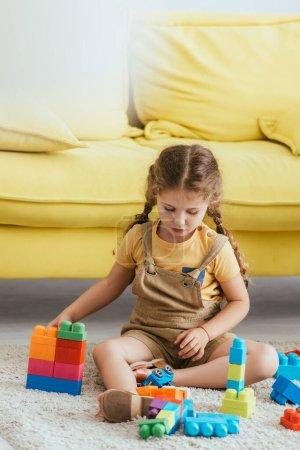 Photo pour Mignon enfant jouer avec des blocs de construction tout en étant assis sur le sol près du canapé jaune - image libre de droit