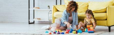 Photo pour Concept horizontal de baby-sitter et mignon enfant jouer avec des blocs de construction multicolores sur le sol - image libre de droit
