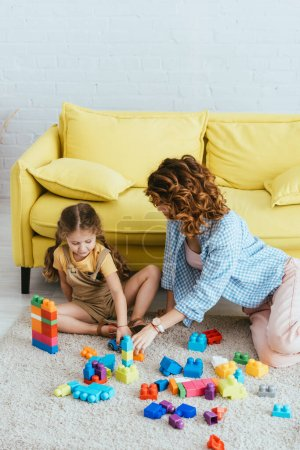 Photo for Young nanny and cute child playing with multicolored building blocks on floor near yellow sofa - Royalty Free Image