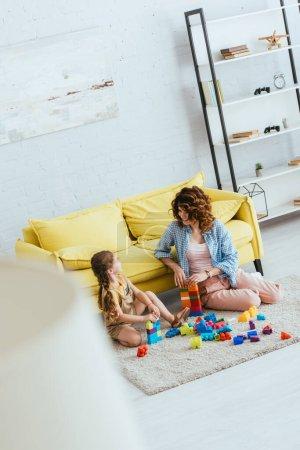 Photo pour Foyer sélectif de nounou et adorable enfant jouer avec des blocs de construction multicolores sur le sol dans le salon, vue grand angle - image libre de droit