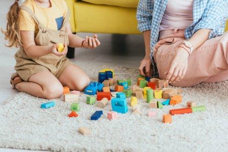 Photo pour Vue recadrée de l'enfant tenant des blocs multicolores près de nounou tout en jouant sur le sol - image libre de droit