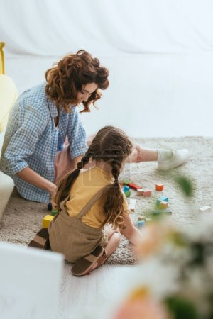 selective focus of babysitter and kid sitting on floor and playing with multicolored blocks