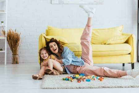 Photo for Cheerful nanny with raised leg having fun with happy child on floor near multicolored blocks - Royalty Free Image