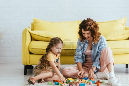 Photo for Smiling nanny and cute child sitting on floor and playing with multicolored blocks - Royalty Free Image