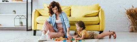 concepto panorámico de niñera joven y adorable niño jugando con bloques multicolores en el suelo en la sala de estar