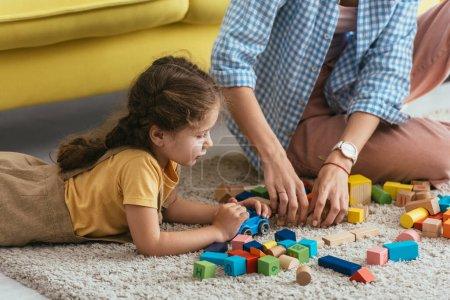 Photo pour Vue recadrée de nounou et enfant jouer avec des blocs multicolores de plancher - image libre de droit