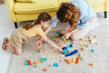 high angle view of babysitter and kid playing with multicolored blocks and toy car on floor