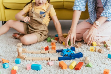 partial view of child and nurse playing with multicolored blocks and toy car on floor