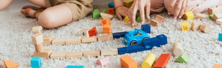 partial view of nanny and child near multicolored cubes and toy car on floor, panoramic shot