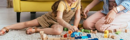 cropped view of babysitter near child playing with toy car near multicolored blocks on floor, horizontal image