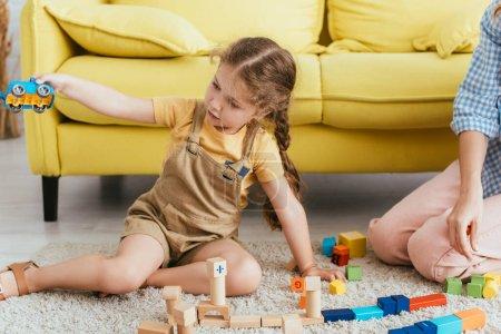 Photo pour Vue recadrée de baby-sitter près d'enfant tenant voiture jouet tout en étant assis sur le sol près de blocs multicolores - image libre de droit